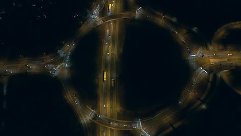 Aerial, vertical - Illuminated roundabout with traffic at night Footage