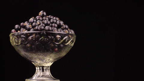 Rotation of a heap of black currants in a glass vase Footage