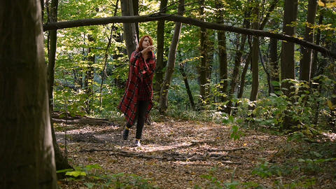 Young girl wrapped in a plaid. Walking alone at forest. the overall plan Footage