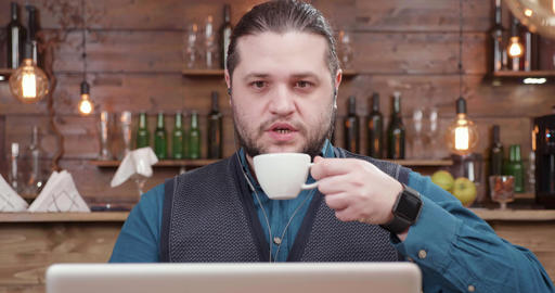 Young businessman in a small coffee shop drinks coffee during a video call Footage