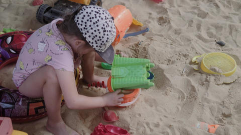 Little Girl Playing In Sandbox with sand and toys Footage