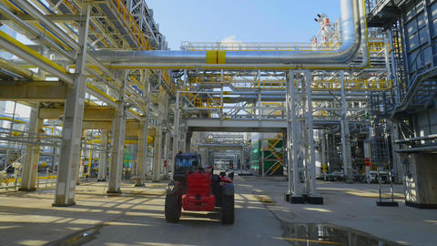 tractor drives along gas and oil refinery plant area on day Archivo