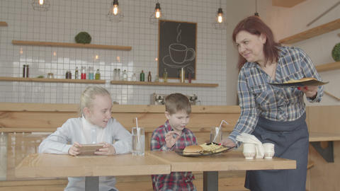 Kids with phones rejoicing fast food meal in cafe Live Action