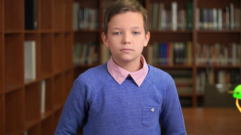 portrait shot of the sad, unhappy schoolboy standing near the bookshelf in the Footage