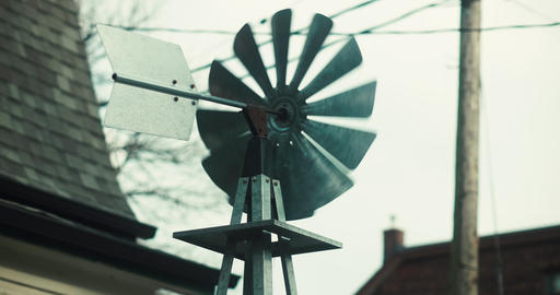 Establishing shot a handcrafted windmill in the front yard of a residence Footage