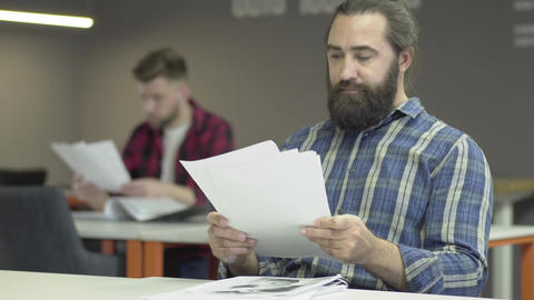 Colleagues read papers with work plans. One office worker or businessman is Footage
