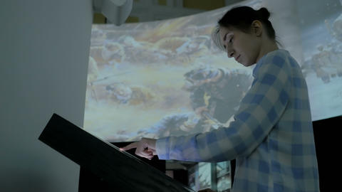 Woman using interactive touchscreen display at modern history museum Footage