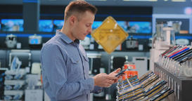 Young handsome man in blue shirt chooses a new mobile phone in an electronics Footage