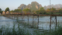 Motorcycle over and motorboat under bridge,Vang Vieng,Laos Footage