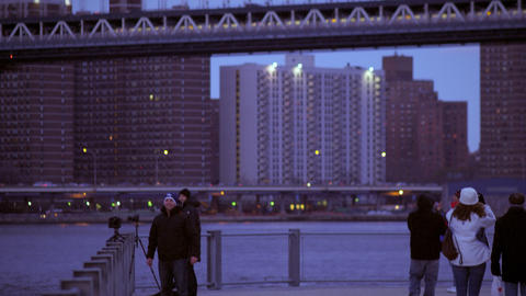 Panning shot of tourists taking pictures and videos of the Brooklyn bridge in Ne Footage
