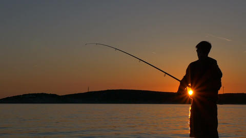 Slow motion - Silhouette of a fisherman at sunset Footage