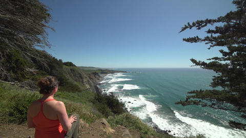Crane shot of woman hiker enjoying Big Sur coastline Footage