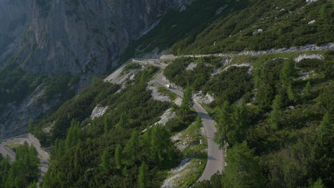 Aerial - Car driving over hairpin turns on mountain road Footage