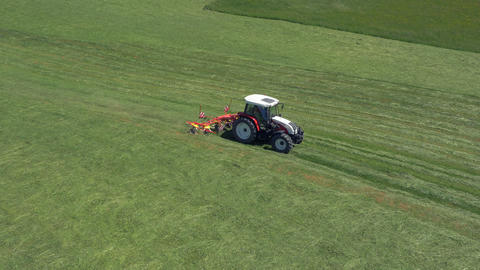 Aerial - Tractor tossing and turning grass to make hay for silage Footage