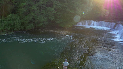 Aerial - Mature man fly fishing at sunset Footage