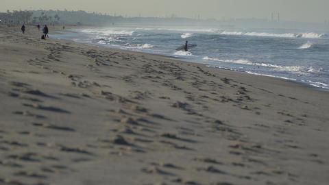 Surfer walks into ocean near the Santa Monica Pier Footage