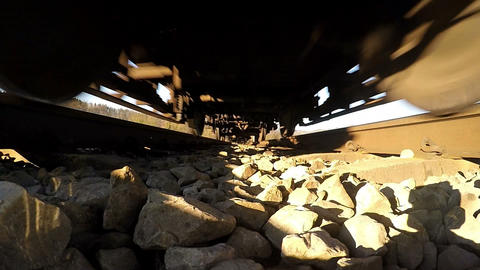 Rail track POV - Undercarriage of moving locomotive, slow motion Footage