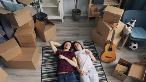 Husband and wife talking about interior lying on floor in... Stock Video Footage