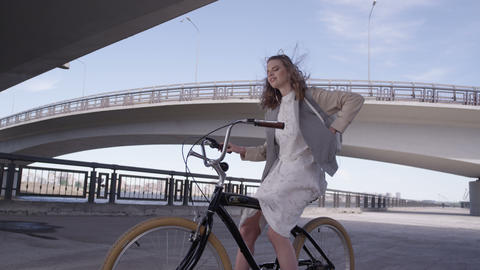 girl in dress takes out smartphone on bike slow motion GIF