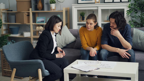 Housing agent showing house plans to beautiful couple talking indoors at home Footage