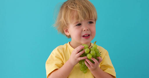 Healthy eating concept with child eating grapes Footage