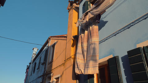 Bed linen fluttering in the wind on one of the facades of italian Burano Live Action