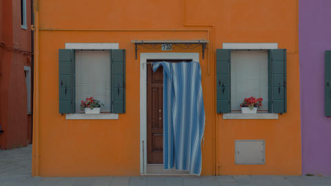 A bright yellow facade of a small house in Burano, Italy Live Action