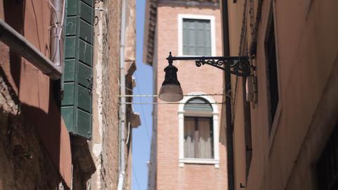 A wall mounted streetlight on a narrow Venice street Live Action