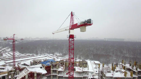 A working construction crane above the building construction area Live Action