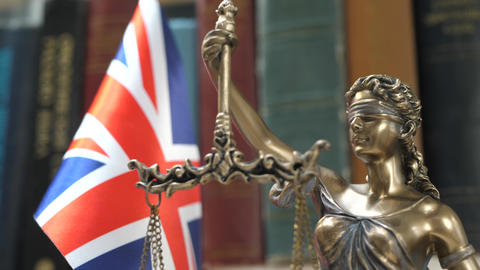 Statue of Lady Justice with Bookshelf with Books and UK Flag Background Footage