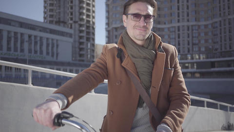 Handsome smiling man in sunglasses and brown coat standing with his bicycle in Live Action