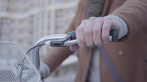 Hand of the man presses the handbrake on the bike close up. Urban cityscape in Footage