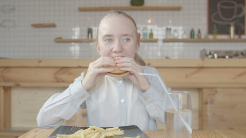 Preteen girl eating burger with appetite in cafe Live Action