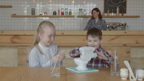 Joyful carefree children playing toy on cafe table Live Action