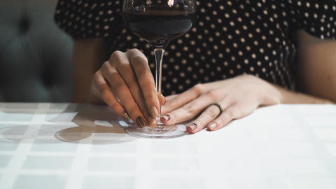 Elegant women's hands embarrassingly take a glass of wine in a restaurant Footage