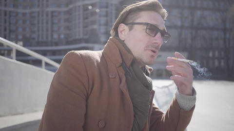 The guy smoking cigarette. Leisure of the attractive guy. Cityscape in the Footage