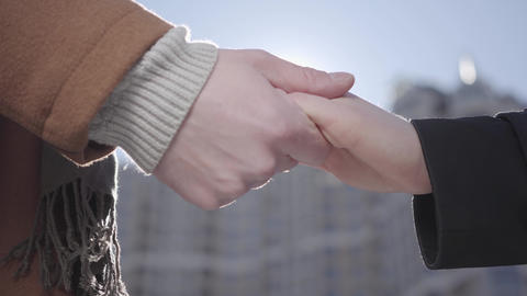 Man and woman hands close up in front of urban cityscape. The man holding hands Footage
