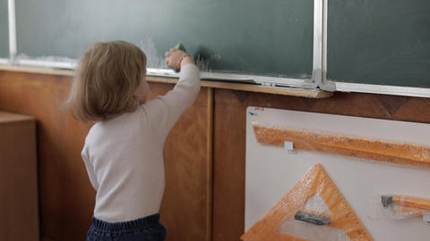 Girl cleaning blackboard using a washcloth in classroom. Education process Footage