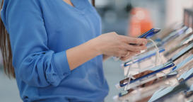 Close-up woman in an electronics store holding a new smartphone picks before Archivo