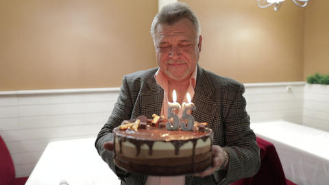 Happy respectable old man holding cake. Celebrating. Blowing birthday candles Footage