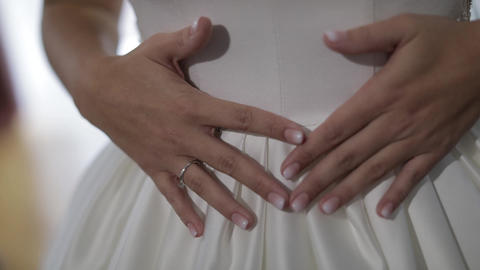 Bride in wedding dress. Hand touches dress. Pretty and well-groomed woman Footage