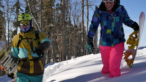 Happy Young Couple walks with Snowboard on deep snow in Wild Winter Mountains Footage