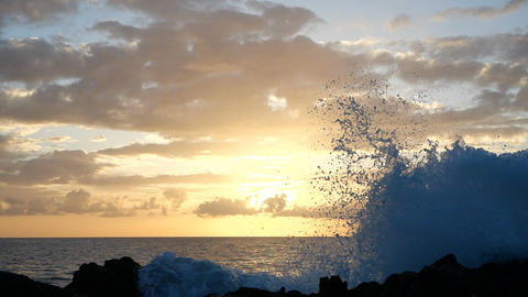 Waves rise in the air at beautiful sunset light. Big wave is crashing on rocks Footage