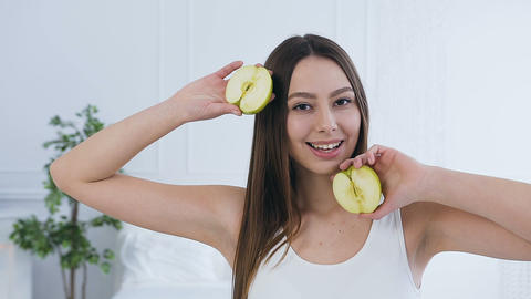 Portrait shot of beautiful young woman posing with two half of apple Live Action