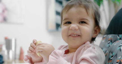 Baby girl attemtping to eat a cookie by herself Footage
