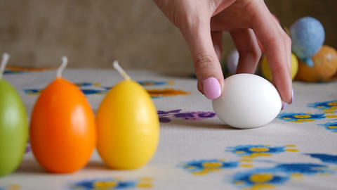Easter. Female hand spin white egg on the table. Colorful Easter eggs in the Archivo