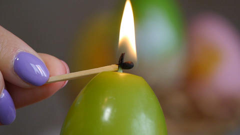Candles made in shape of easter egg. Green candles. Female hand lights candles Live Action