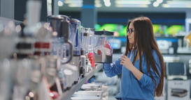 Young beautiful woman in the appliances store is choosing for its kitchen a Footage