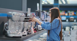 In the appliances store, a brunette woman in a shirt chooses a blender for Footage