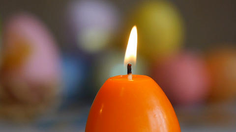 Candles made in shape of easter egg. Burning candles. Green and orange candles Live Action